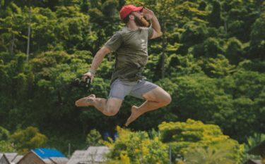 ジャンプして土地を探す男性